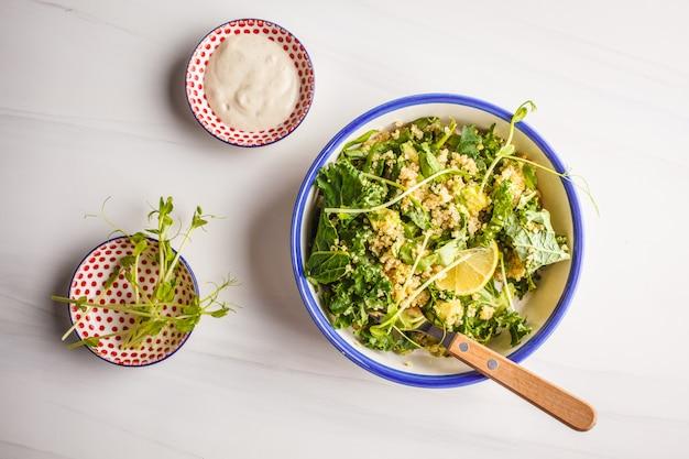 Insalata di kale, quinoa, avocado vegan in una ciotola bianca su sfondo bianco.