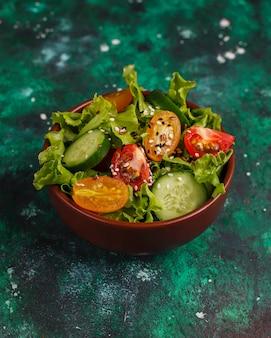 Insalata di lattuga fresca con pomodori gialli, fette, pomodorini, ciotola di semi sul buio,