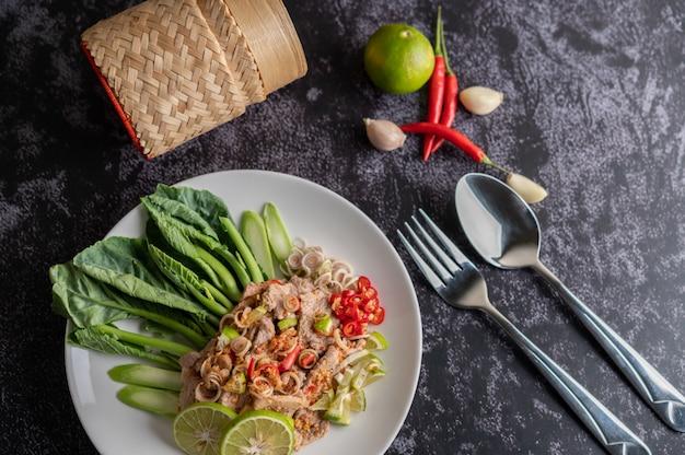Insalata di maiale piccante lime con cavolo, galanga, peperoncino e aglio in un piatto bianco su un pavimento di cemento nero.