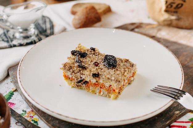 Insalata di maionese con verdure prugne secche all'interno del piatto bianco e pagnotte di pane