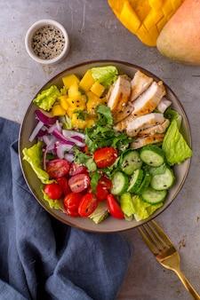 Insalata di mango di pollo alla griglia con coriandolo, cetrioli, pomodorini e cipolla rossa