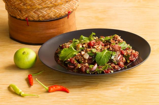 Insalata di manzo in un piatto nero su un tavolo di legno (carne fresca nel sangue), spazio per l'immissione di testo.