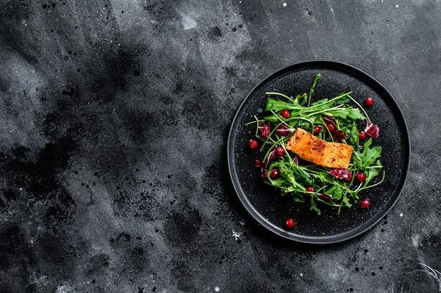 Insalata di mare con salmone, rucola, lattuga e mirtilli rossi. copia spazio