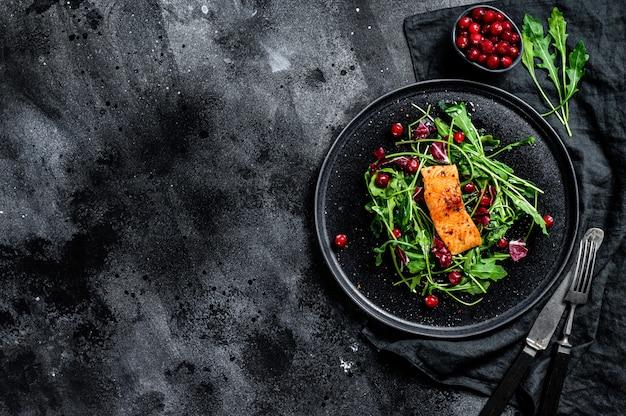Insalata di mare con salmone, rucola, lattuga e mirtilli rossi. vista dall'alto