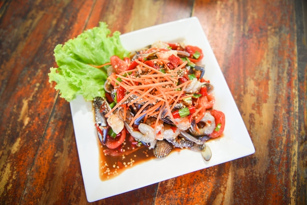 Insalata di mare speziata con gamberetti freschi granchi di granchio servita su piatto bianco verdure fresche erbe e spezie ingredienti con insalata di carote lattuga som tum menu tailandese asiatico