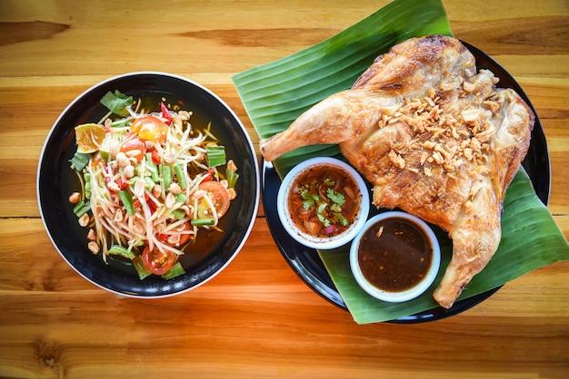 Insalata di papaia e pollo alla griglia con salsa servita sul piatto sul tavolo in legno som tum menu thai food asian