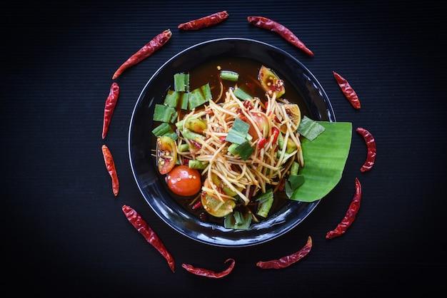 Insalata di papaia insalata di papaya verde piccante cibo tailandese con erbe e spezie ingredienti con peperoncino