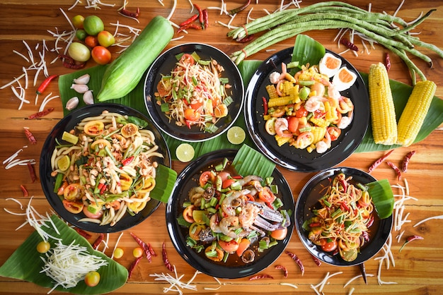 Insalata di papaia servita sul tavolo da pranzo. alimento tailandese piccante dell'insalata verde della papaia sul piatto con gli ortaggi freschi.