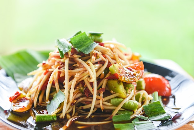 Insalata di papaia servita sul tavolo da pranzo insalata di papaya verde piccante cibo tailandese sul piatto con erbe e spezie ingredienti som tum menu tailandese cibo asiatico