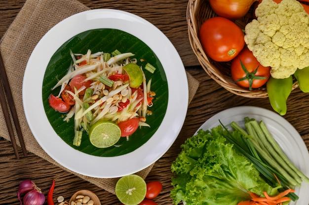 Insalata di papaia (som tum tailandese) su un piatto bianco su un tavolo di legno.