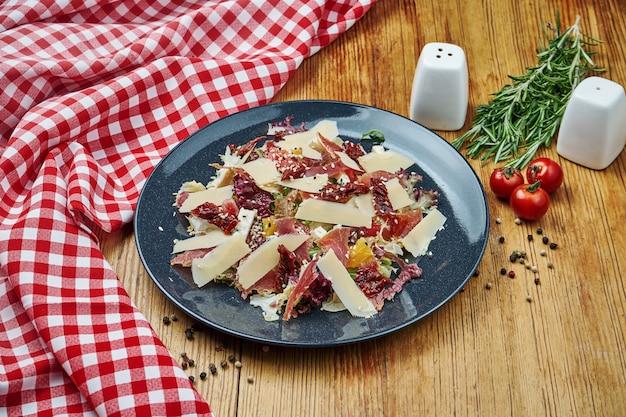 Insalata di parmigiano, arancia, lattuga e jamon in banda nera su legno.