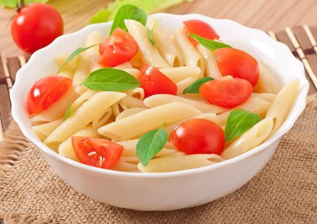 Insalata di pasta con pomodorini e foglie di basilico fresco