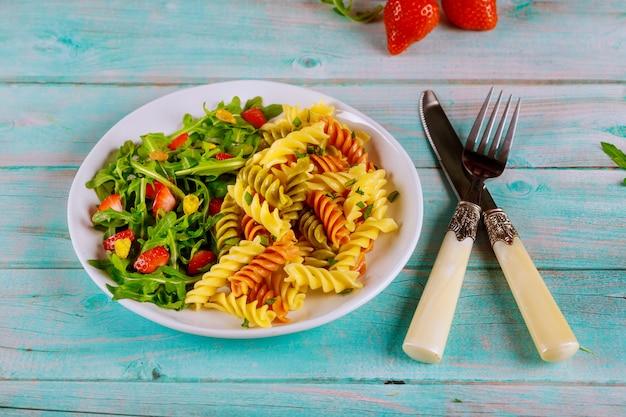 Insalata di pasta e rucola rotini con fragole e pistacchi sul tavolo blu