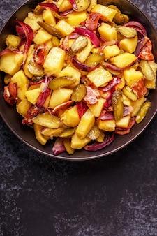 Insalata di patate fatta in casa con pancetta e sottaceti.