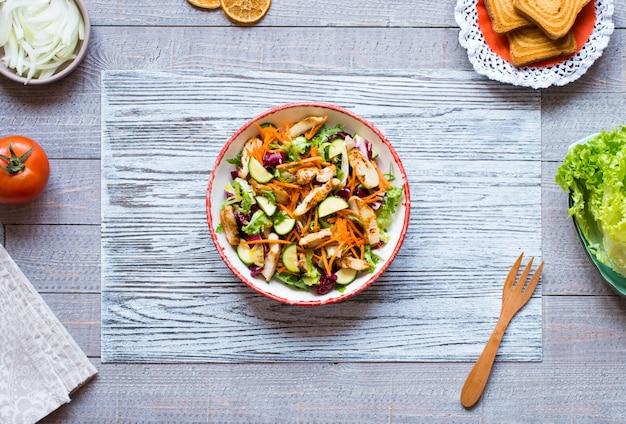 Insalata di petto di pollo con zucchine e pomodorini, su una superficie di legno