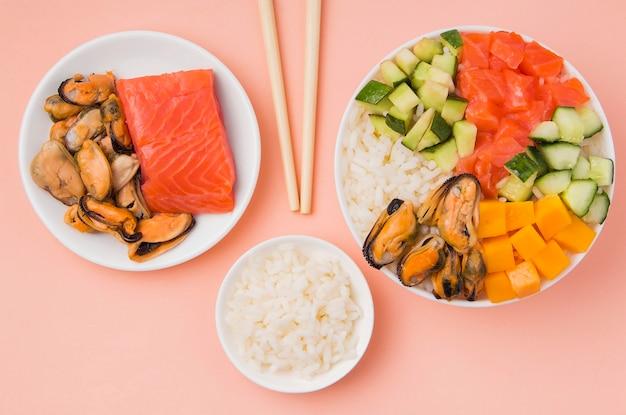 Insalata di poke tradizionale in una ciotola su uno sfondo rosa accanto a bacchette e ingredienti.