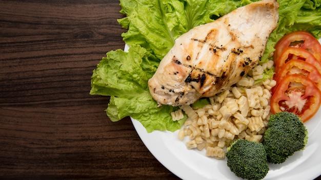 Insalata di pollo al seno servire con verdure fresche sul piatto bianco.