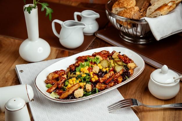Insalata di pollo alla griglia con fette biscottate lattuga mais cetriolo salato pepe e pane sul tavolo
