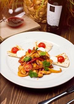 Insalata di pollo fresca con condimento di verdure, pane caucasico arabo su un piatto bianco. menu dietetico nutrizione appropriata.
