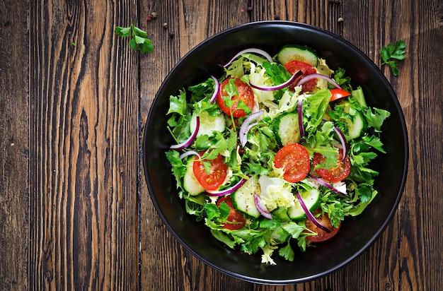 Insalata di pomodori, cetrioli, cipolle rosse e foglie di lattuga. menù vitaminico estivo salutare. alimenti vegetali vegani. tavolo da pranzo vegetariano. vista dall'alto. disteso