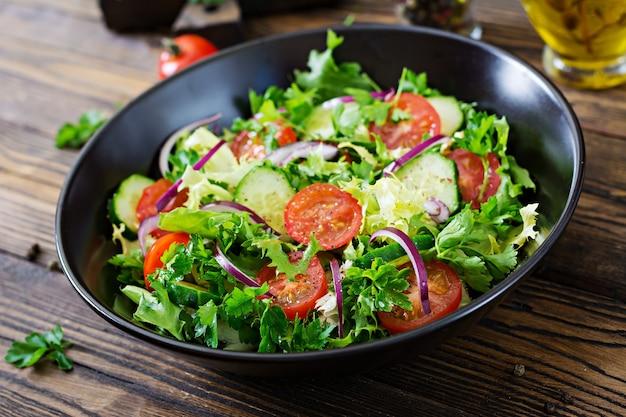 Insalata di pomodori, cetrioli, cipolle rosse e foglie di lattuga. menù vitaminico estivo salutare. alimenti vegetali vegani. tavolo da pranzo vegetariano.