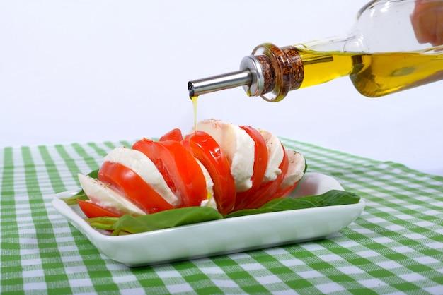 Insalata di pomodori con bottiglia di olio d'oliva