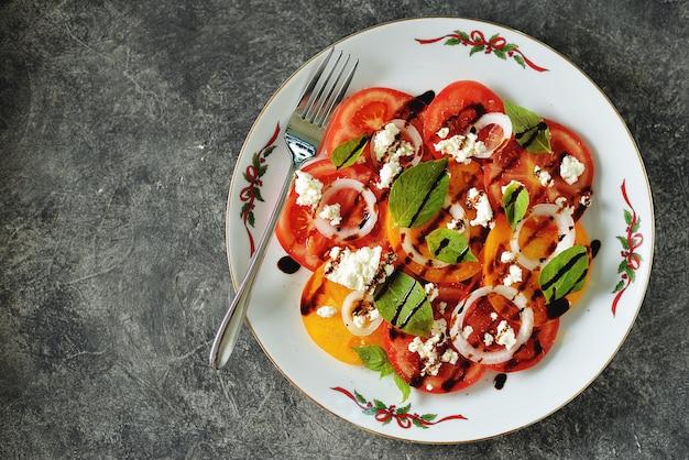 Insalata di pomodori gialli e rossi con basilico, formaggio a pasta molle e cipolle