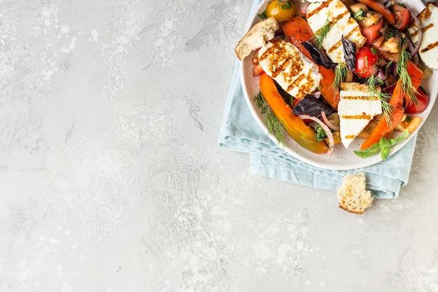 Insalata di pomodori, pepe e cipolla al forno con formaggio grigliato