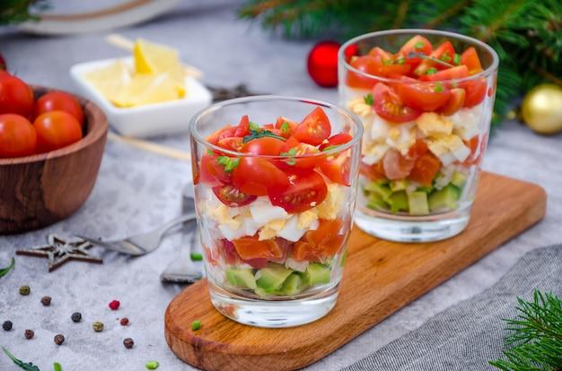 Insalata di porzioni con salmone affumicato, avocado, uovo, pomodorini con salsa di crema di formaggio