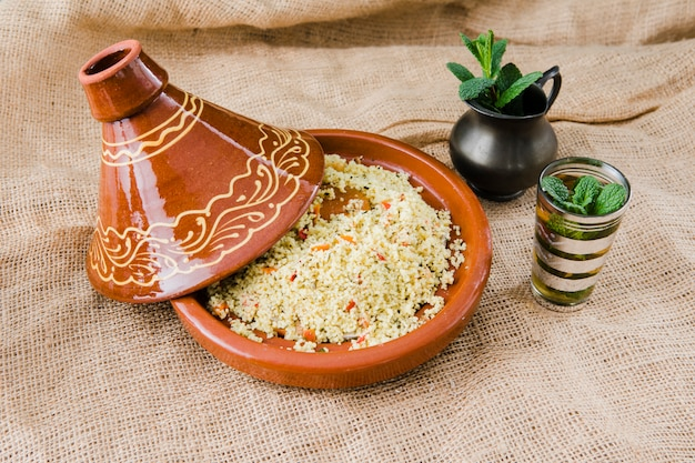 Insalata di quinoa in ciotola vicino a tazza e brocca