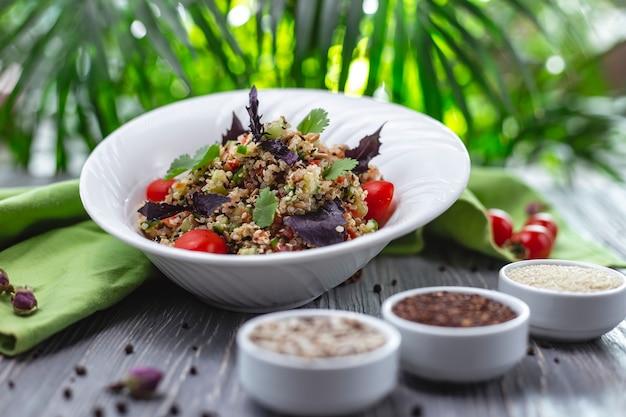 Insalata di quinoa vista laterale con cetriolo pomodoro e sale e pepe di basilico sul tavolo