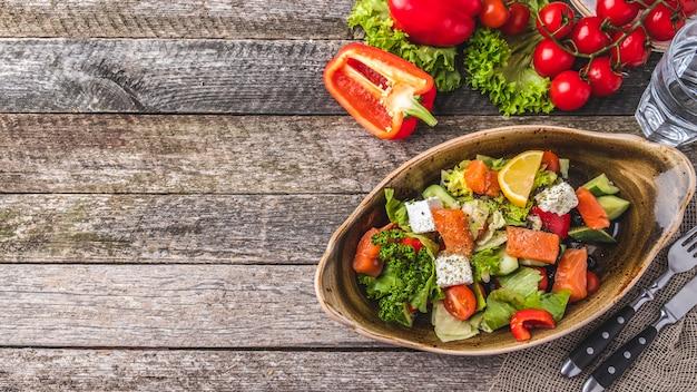 Insalata di salmone peperoncino, pomodorini, insalata, formaggio, cetriolo e olive nere. vista dall'alto.