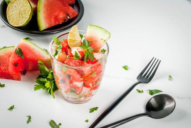 Insalata di salsa di verdure con anguria, pomodori, cipolle, verdure, lime in vetro porzionato