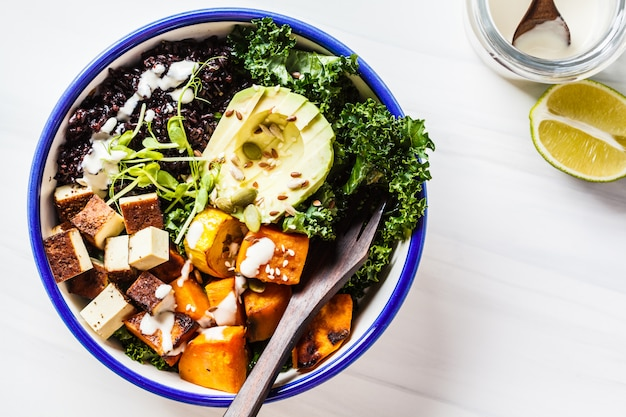 Insalata di scodella di buddha con riso nero, avocado, tofu, patate dolci, cavolo nero e salsa tahini