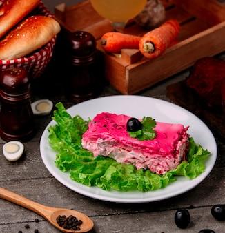 Insalata di shuba con aringhe con olive sul tavolo