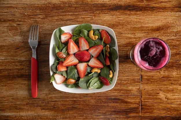Insalata di spinaci e fragole con succo di barbabietola sul tavolo di legno