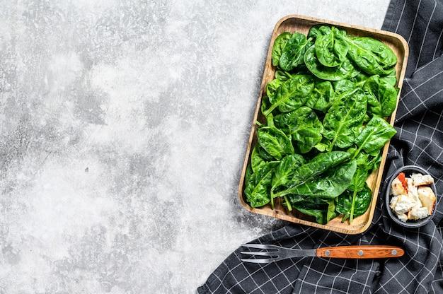 Insalata di spinaci freschi in una ciotola di legno con formaggio di capra.