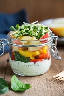 Insalata di spinaci, mela e pomodoro ciliegia in un barattolo con salsa alle erbe yogurt