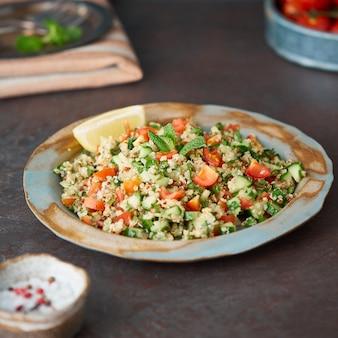 Insalata di tabulé con quinoa. il cibo orientale con verdure si mescola
