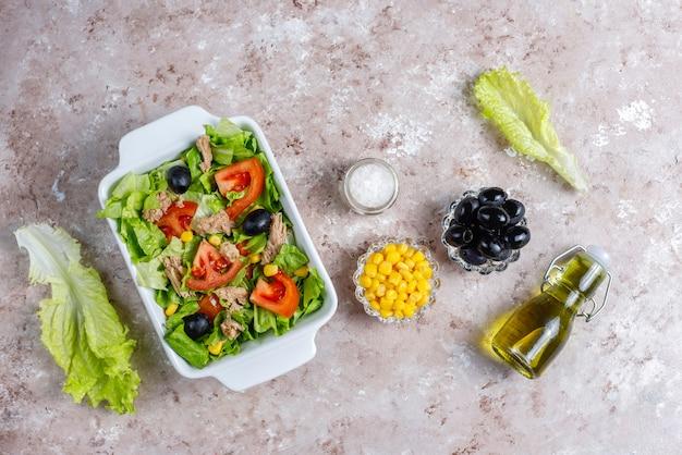 Insalata di tonno con lattuga, olive, mais, pomodori, vista dall'alto