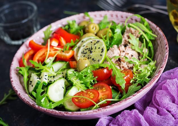 Insalata di tonno con pomodori, olive, cetrioli, peperoni e rucola su fondo rustico