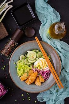 Insalata di uova, pesce fritto e verdure fresche. cucina asiatica. vista dall'alto