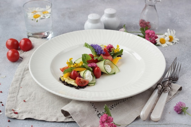 Insalata di verdure colorata decorata con fiori su un piatto bianco