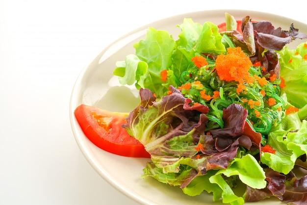 Insalata di verdure con alghe giapponesi e uova di gamberetti su sfondo bianco