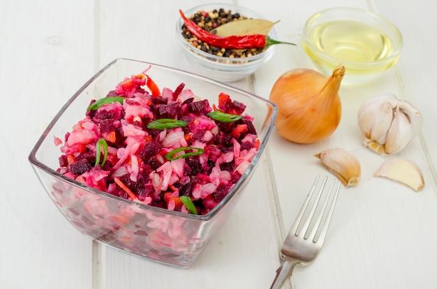 Insalata di verdure con barbabietole, spezie, cipolle, aglio sul tavolo di legno