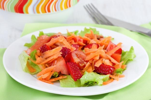 Insalata di verdure con fragole sul piatto bianco