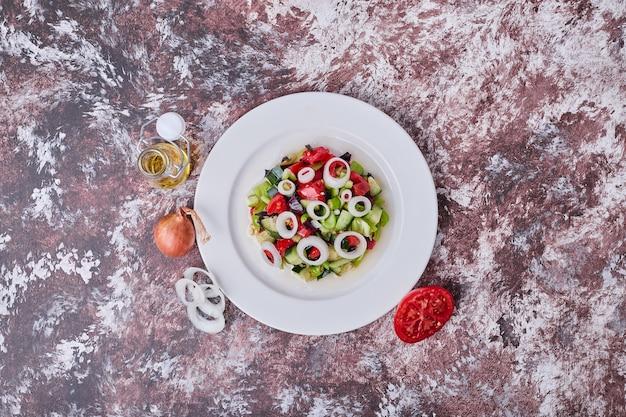 Insalata di verdure con ingredienti tritati e tritati in un piatto bianco, vista dall'alto