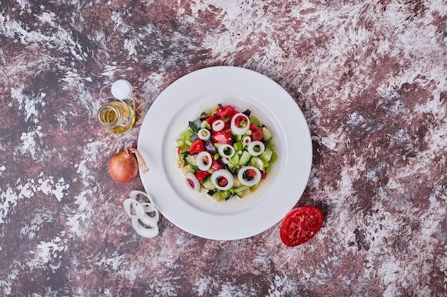 Insalata di verdure con ingredienti tritati e tritati sul tavolo.
