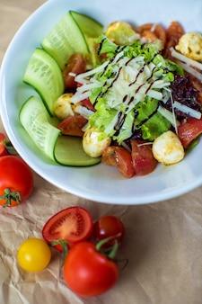 Insalata di verdure con lattuga, pomodoro bollito, cetriolo e funghi con formaggio grattugiato