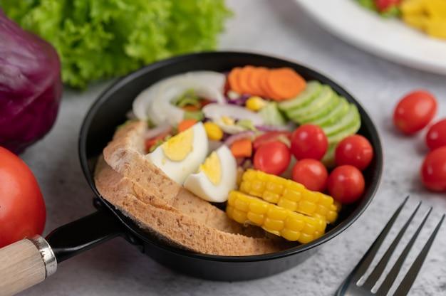Insalata di verdure con pane e uova sode in padella.